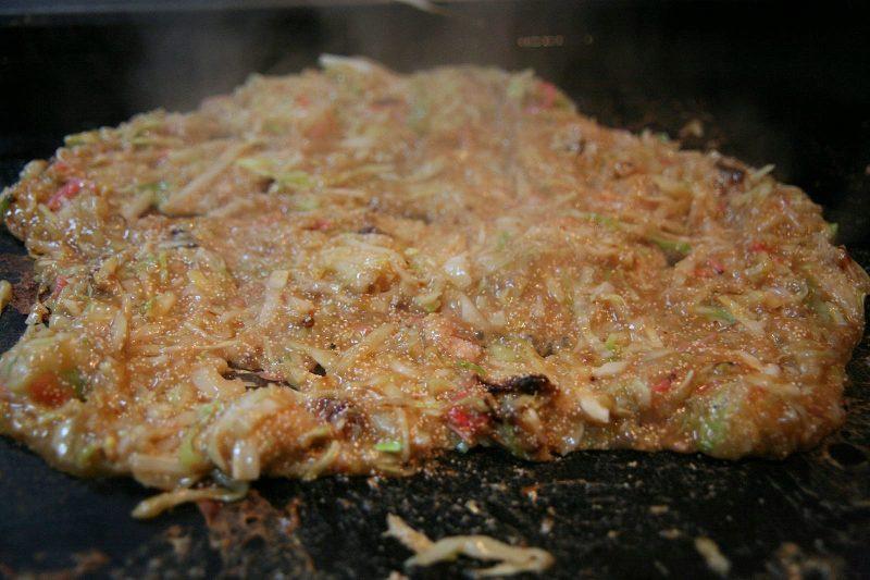 Có nhiều điểm tương đồng với Okonomiyaki, nhưng Monjayaki không được nướng kỹ và khô như Okonomiyaki