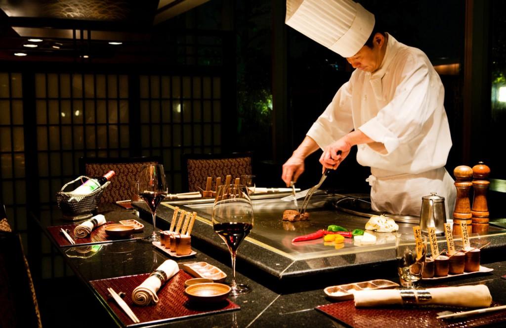 """Tên gọi Teppanyaki đơn giản chỉ mang nghĩa """"nướng trên bản sắt"""". Các đầu bếp thường biểu diễn quá trình chế biến món ăn Teppanyaki ngay trước mặt thực khách"""